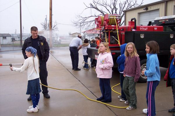 Student Using Hose by Truck